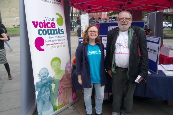 A volunteer in front of the Healthwatch stall