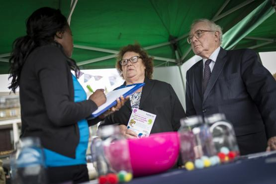 People speaking to a member of Healthwatch staff at a Healthwatch stall