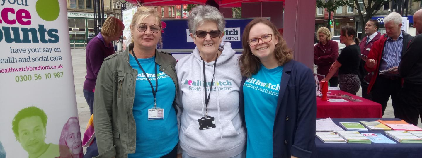 Three volunteers stood by the Healthwatch stand